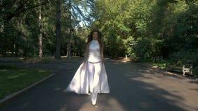 Une belle femme dans un costume blanc marche rapidement et court en parc de ville banque de vidéos