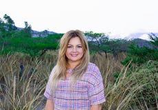 Une belle femme dodue dans une robe courte Blond Avec un beau sourire Dehors sur la prairie et les montagnes dans le backgro photos libres de droits