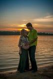 Une belle femme enceinte avec son mari sur la plage de berge souriant et touchant son ventre avec l'amour et soin Image libre de droits