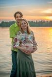 Une belle femme enceinte avec son mari sur la plage de berge souriant et touchant son ventre avec l'amour et soin Image stock