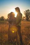 Une belle femme enceinte avec son mari sur le paysage de nature souriant et touchant son ventre avec l'amour et soin heureux Photo stock