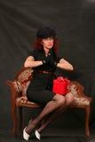 Une belle femme entre deux âges avec un cadeau rouge Image libre de droits