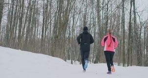 Une belle femme et un homme courent dans la forêt dans la nutrition appropriée d'hiver et un mode de vie sain Mouvement lent banque de vidéos
