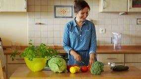 Une belle femme fait cuire dans la cuisine Elle est dans l'excellente humeur, elle danse et rit Mouvement lent clips vidéos