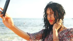 Une belle femme prend des photos avec son téléphone portable sur la plage banque de vidéos