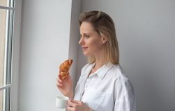 Une belle femme regarde la fenêtre Café de matin de boissons avec le croissant image stock