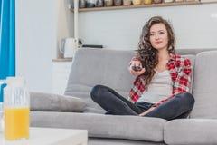 Une belle femme regarde la TV et s'assied sur le divan et tient l'à télécommande dans sa main Une brune dans a photo libre de droits