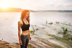 Une belle femme sportive se tenant sur le rivage d'un lac dans le spor photographie stock libre de droits
