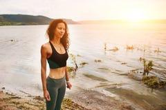 Une belle femme sportive se tenant sur le rivage d'un lac dans le spor photos stock