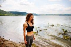 Une belle femme sportive se tenant sur le rivage d'un lac dans le spor photos libres de droits