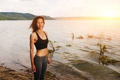 Une belle femme sportive se tenant sur le rivage d'un lac dans le spor photo stock