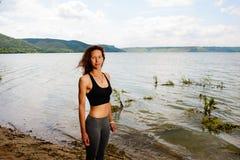 Une belle femme sportive se tenant sur le rivage d'un lac dans le spor image stock