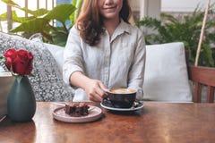 Une belle femme tenant et buvant du café chaud de latte avec le gâteau de 'brownie' sur la table en café photographie stock