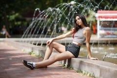 Une belle fille attrayante avec la longue allocation des places de cheveux au bord de la fontaine sur un fond brouillé naturel Photos libres de droits
