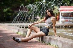 Une belle fille attrayante avec la longue allocation des places de cheveux au bord de la fontaine sur un fond brouillé naturel Image libre de droits