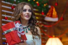 Une belle fille avec de longs cheveux dans une robe blanche tient une boîte de fête rouge Photo stock