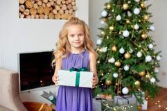 Une belle fille avec les cheveux bouclés blonds se tient dans le salon près de la cheminée et tient son cadeau dans des ses mains image libre de droits