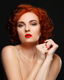 Une belle fille avec les cheveux rouges regarde impatiemment l'appareil-photo Images stock