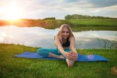 Une belle fille blonde pratique le yoga sur le lac au coucher du soleil plan rapproché il soutient un mode de vie sain Images libres de droits