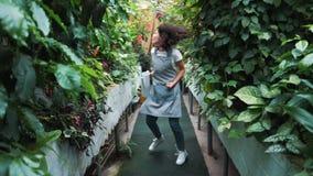 Une belle fille dans une danse de tablier en serre chaude Fleuriste heureux, danse et rire clips vidéos