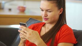 Une belle fille dans une robe rouge écrit un message dans son mobile Alors il regarde le cadre et sourit largement social clips vidéos