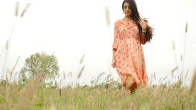 Une belle fille dans une robe se tient parmi l'herbe grande Mouvement lent banque de vidéos