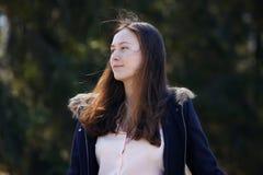 Une belle fille dans un manteau bleu avec les cheveux rougeâtres lâches photographie stock libre de droits