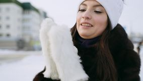 Une belle fille dans un manteau de vison chauffe ses joues avec les mitaines tricotées de fourrure banque de vidéos