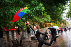 Une belle fille dans un manteau multicolore lumineux par temps pluvieux Photographie stock