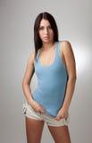 Une belle fille dans un T-shirt bleu avec un CCB gris Images stock