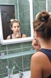 Une belle fille de l'adolescence mettant le rouge à lèvres et vérifiant si elle regarde très bien Photos stock