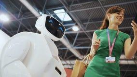 Une belle fille fait le selfie avec un robot Flirts de robot avec la femme Technologies robotiques modernes Le robot regarde banque de vidéos