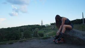 Une belle fille habille des chaussures de sauts d'angoo Elle va faire des sports en parc 4K MOIS lent clips vidéos