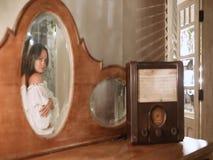 Une belle fille marche après une table avec une radio et des sourires dans le miroir banque de vidéos