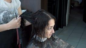 Une belle fille orientale s'assied dans un salon de coiffure tandis qu'un coiffeur se peigne les cheveux humides banque de vidéos