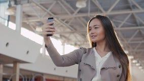 Une belle fille prenant le selfie dans le terminal d'aéroport Jeune femme d'affaires dans le mail avec le téléphone Image libre de droits