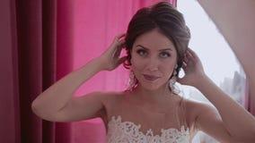 Une belle fille regarde dans le miroir et ajuste ses cheveux Sourire clips vidéos