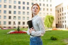 Une belle fille rousse avec des taches de rousseur tient un carnet dans des ses mains et va à l'université Préparation pour des e image libre de droits