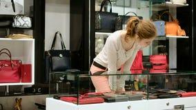 Une belle fille sélectionne un sac magasin de mode de boutique de sac banque de vidéos