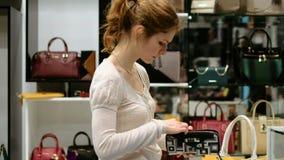 Une belle fille sélectionne un sac magasin de mode de boutique de sac clips vidéos
