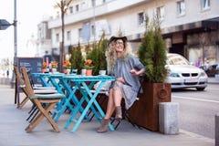 Une belle fille s'asseyant à l'outsite de table et buvant une tasse de Photos stock