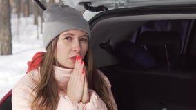 Une belle fille s'assied dans une voiture blanche chauffe ses mains avec le souffle, regarde autour banque de vidéos
