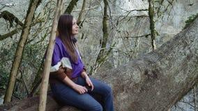 Une belle fille s'assied pensivement sur un arbre dans un verger de buis, examine tout autour et des sourires clips vidéos