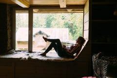 Une belle fille se repose par la grande fenêtre photos libres de droits