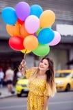 Une belle fille sourit avec beaucoup de ballons à disposition images libres de droits