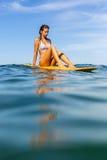 Une belle fille sportive surfant dans l'océan Photographie stock