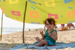 Une belle fille superbe-fantastique sur une plage de mer mange et sourit photo stock