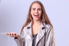 Une belle fille sur un fond gris écoute la musique de son téléphone photos stock