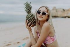 Une belle fille tenant l'ananas et ayant l'amusement sur la plage d'océan photographie stock libre de droits
