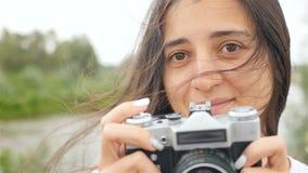 Une belle fille tient une caméra et prend des photos Plan rapproché banque de vidéos